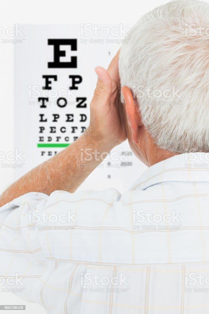 Rear view of a senior man looking at eye chart stock photo