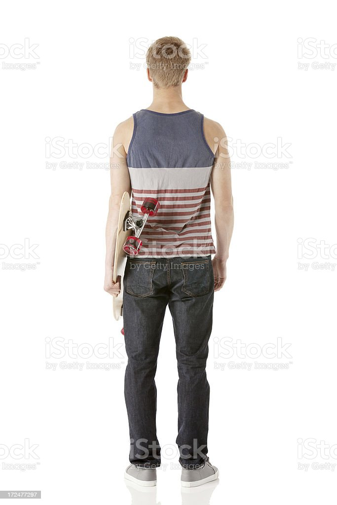 Rear view of a skateboarder with his skateboard royalty-free stock photo