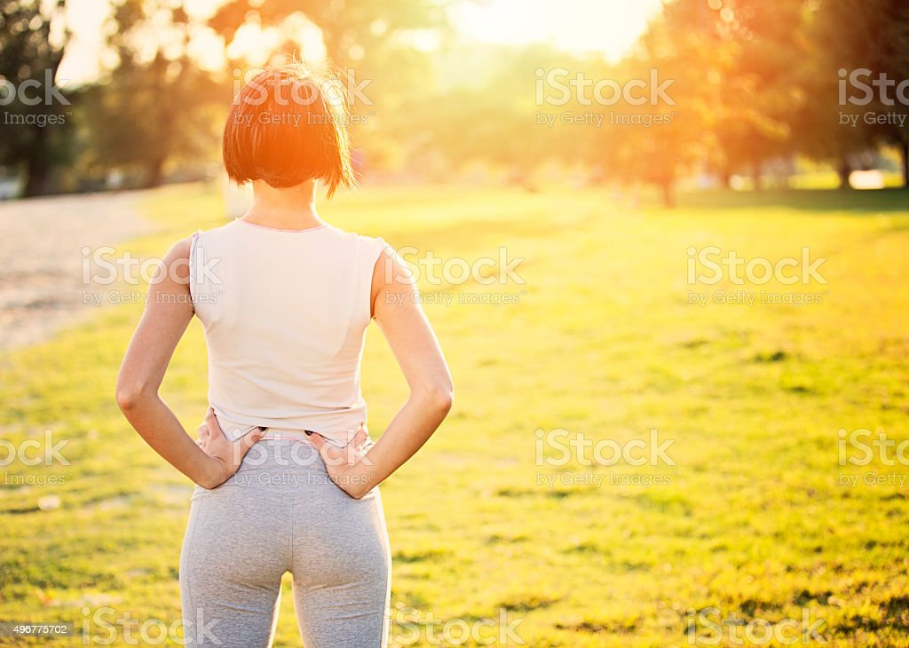 Rear view of a sporty woman in the park stock photo