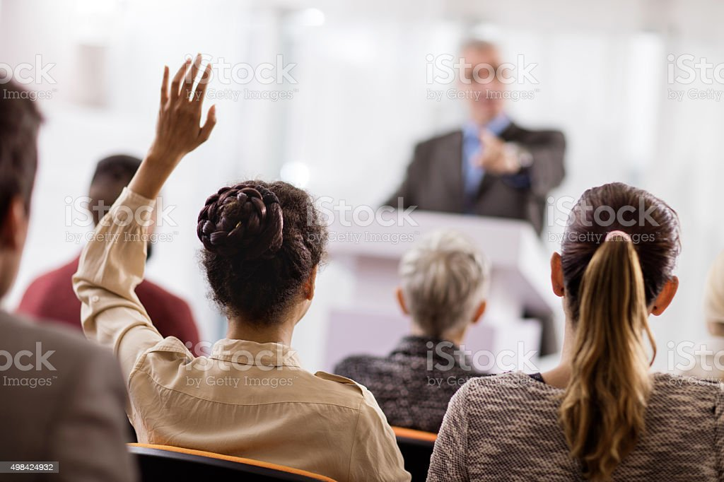 Rear view of a woman asking a question on seminar. stock photo