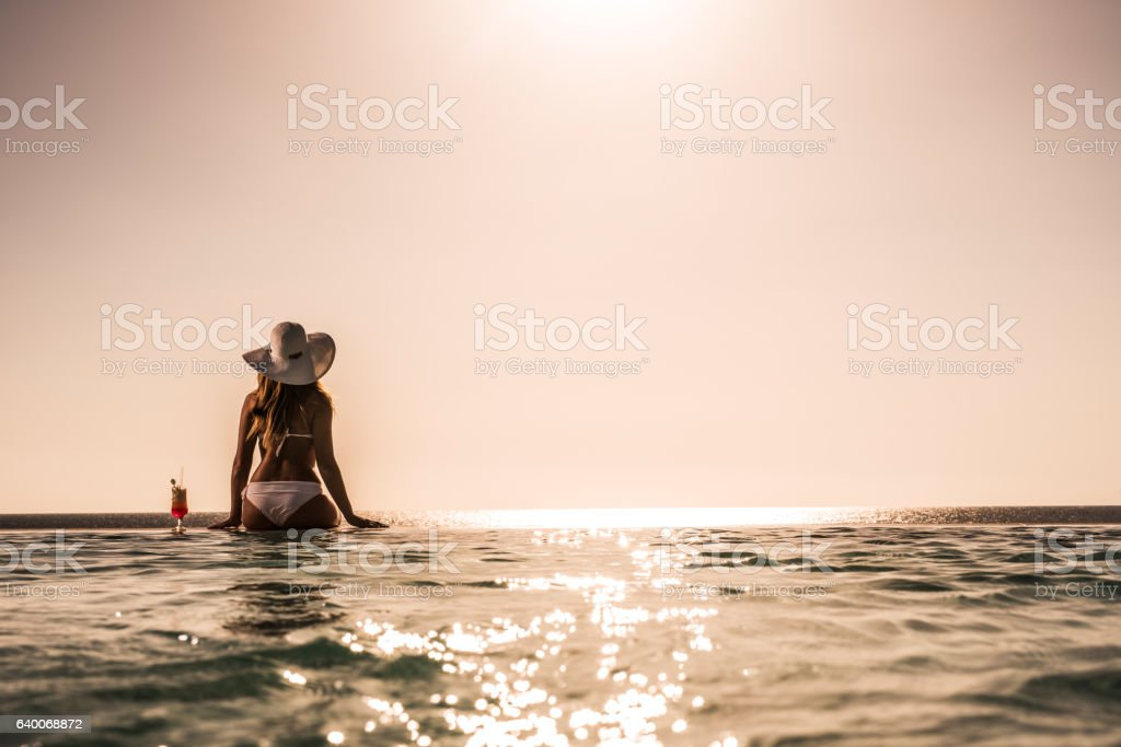 Rear view of a woman at the infinity pool. stock photo