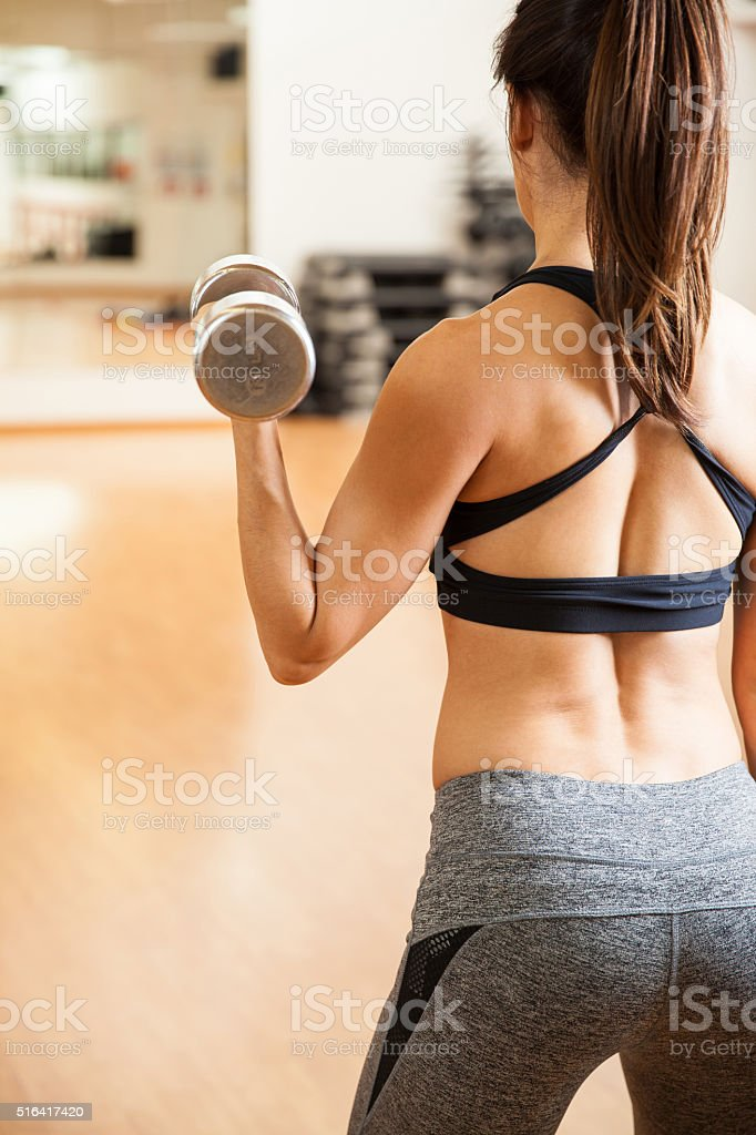 Rear view of a woman doing bicep curls stock photo