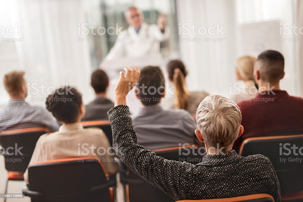 Rear view of a woman from audience asking a question. stock photo