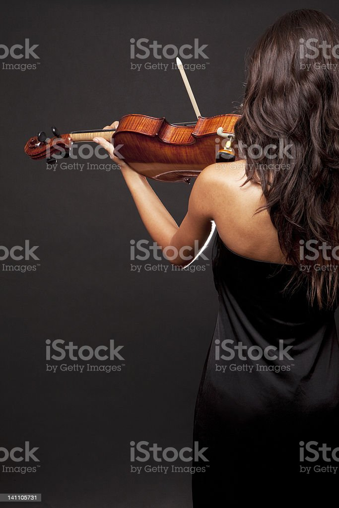 Rear view of a woman in black playing the violin royalty-free stock photo