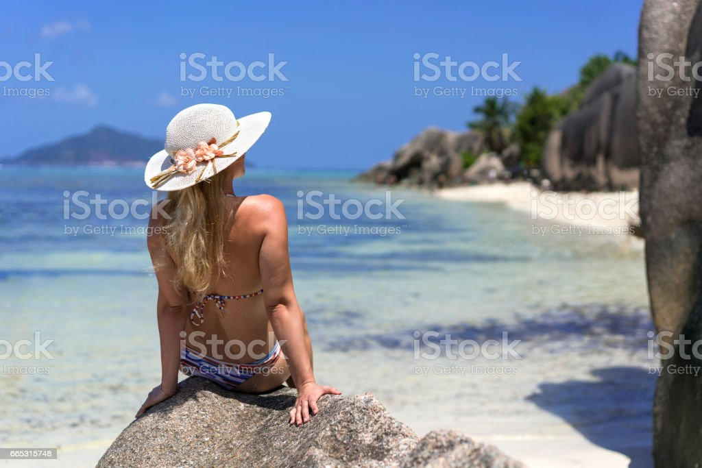 Rear view of a woman relaxing on a beach rock. stock photo