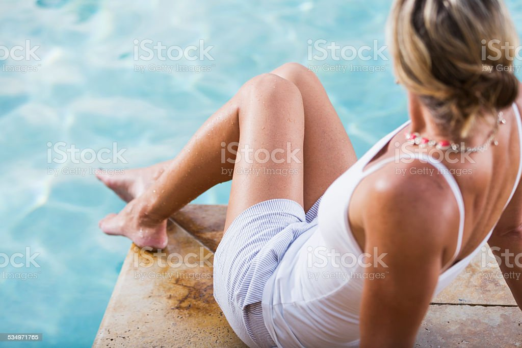 Rear view of a woman sitting by a swimming pool stock photo