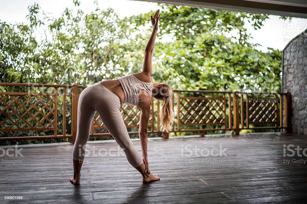 Rear view of a woman stretching on a balcony. stock photo