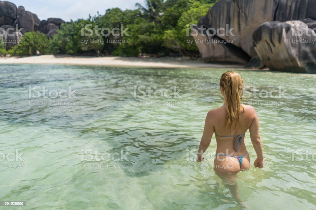 Rear view of a woman walking through the sea. stock photo