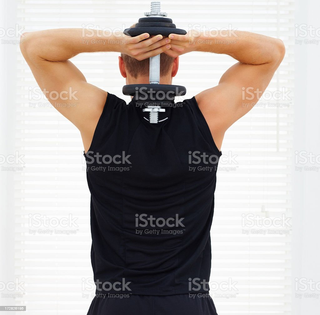 Rear view of a young guy exercising his triceps with a dumbbell stock photo