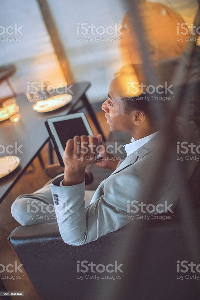 Rear view of a young handsome businessman holding tablet stock photo
