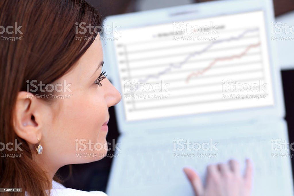 Rear view of a young woman typing at laptop. stock photo