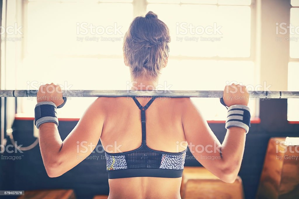 Rear view of active woman in sportswear lifting barbell stock photo