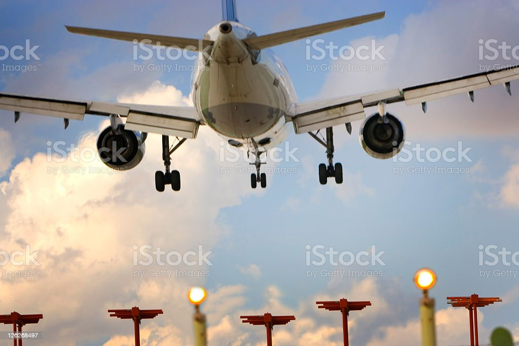 Rear view of airplane on landing approach to airport runway stock photo
