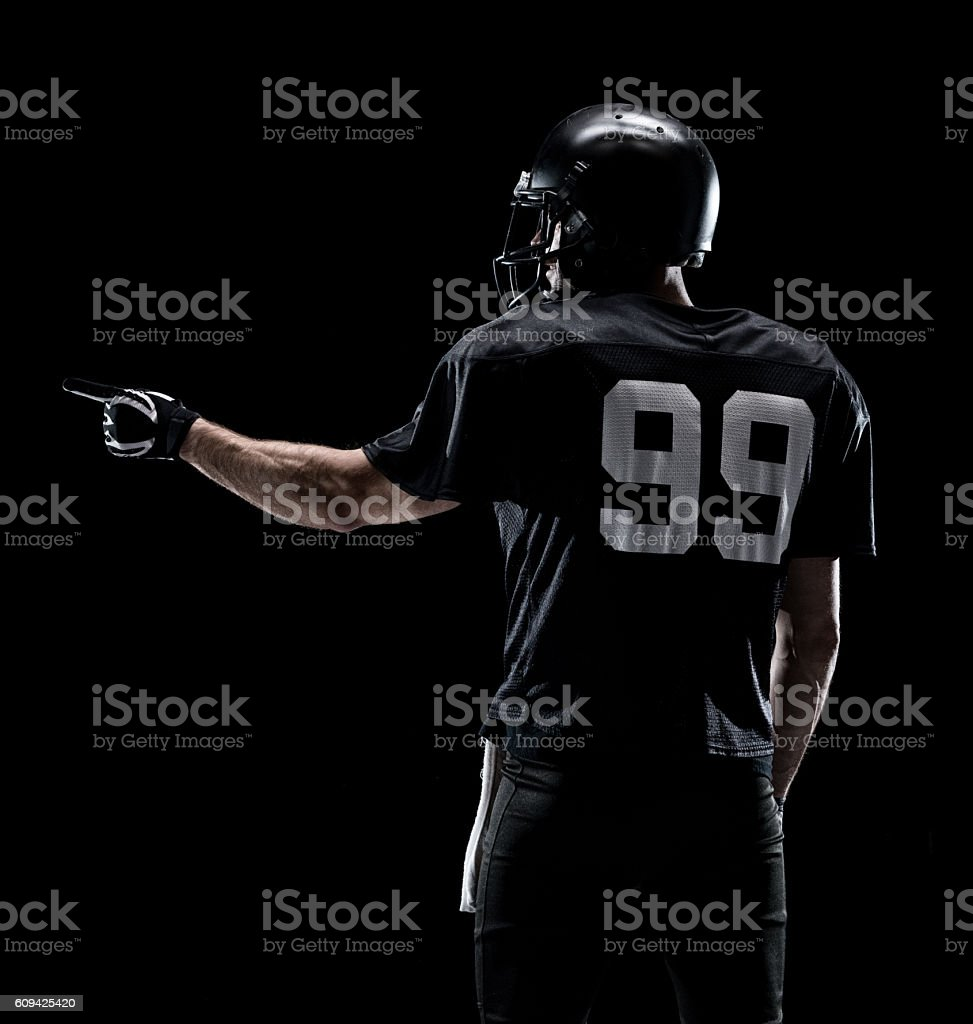 Rear view of American football player pointing stock photo