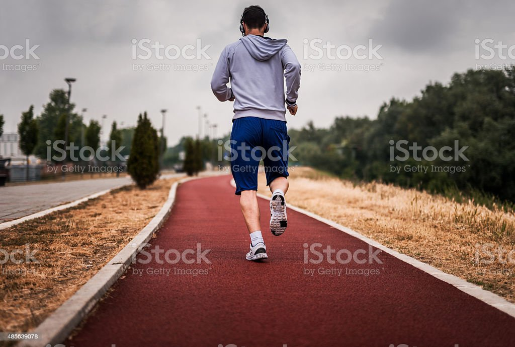 Rear view of an athlete jogging on sports track. stock photo