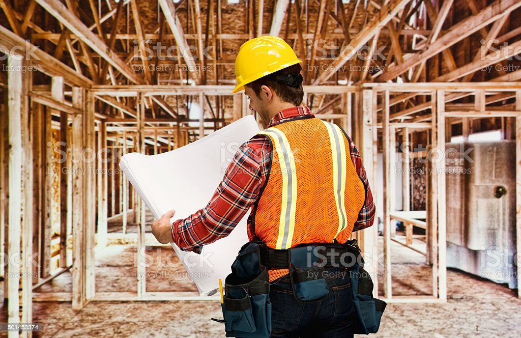 Rear view of architect holding blueprint stock photo