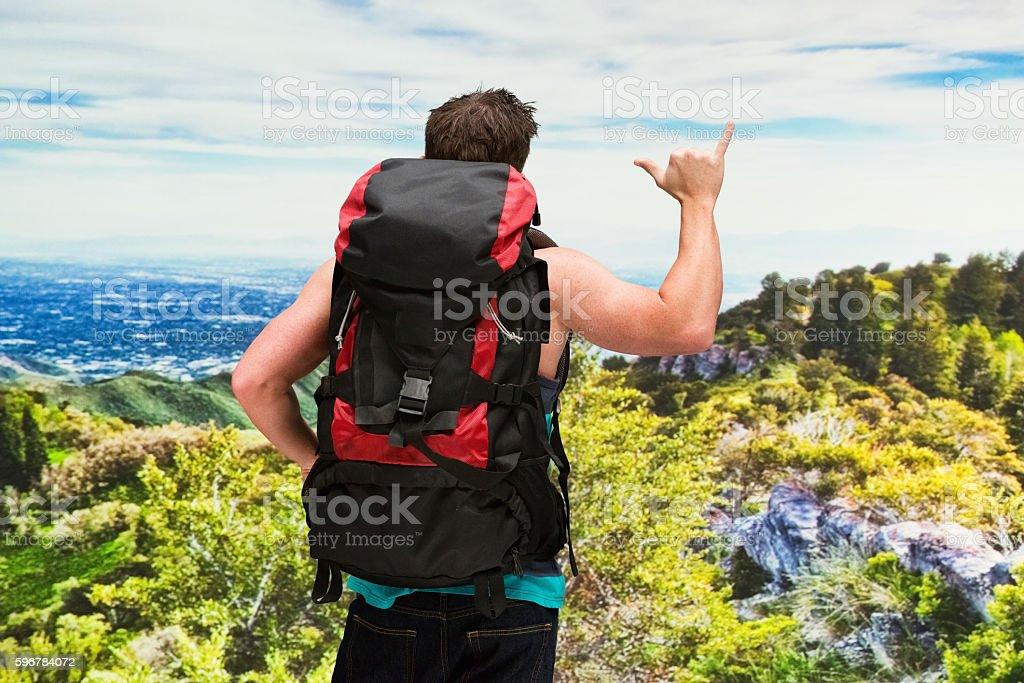 Rear view of backpacker giving shaka sign outdoors stock photo