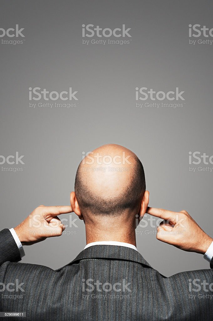 Rear View Of Bald Businessman With Fingers In Ears stock photo
