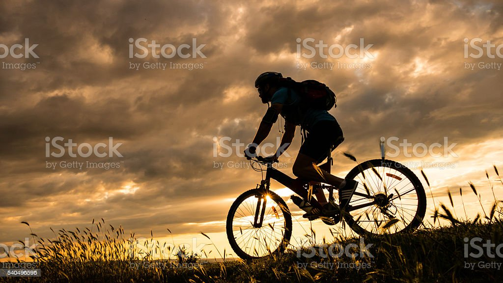 Rear view of biker moving up on the mountain stock photo