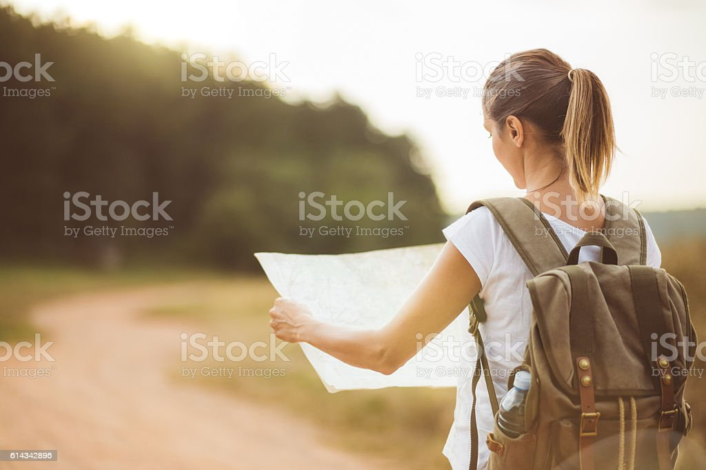 Rear view of blonde girl looking at locatig map stock photo