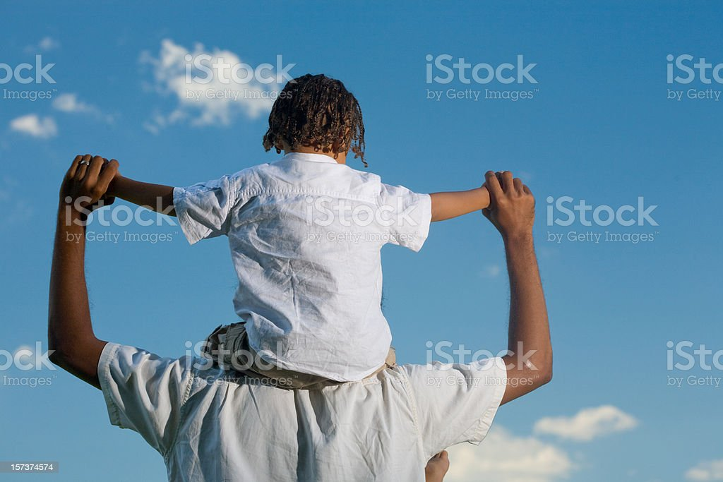 Rear view of boy on dad's shoulders under blue sky royalty-free stock photo