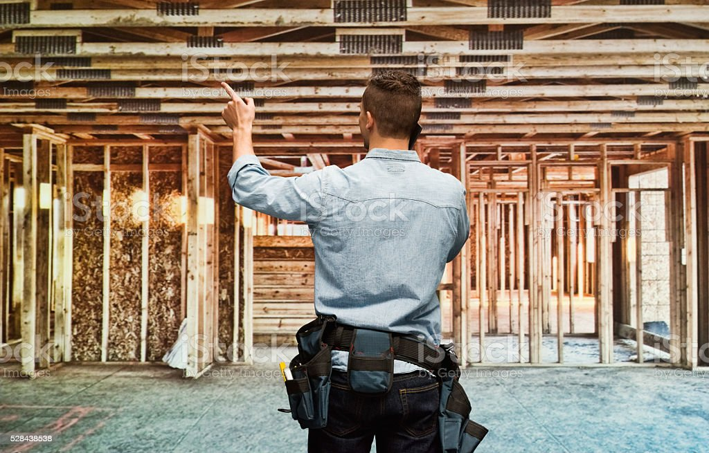 Rear view of building contractor pointing stock photo