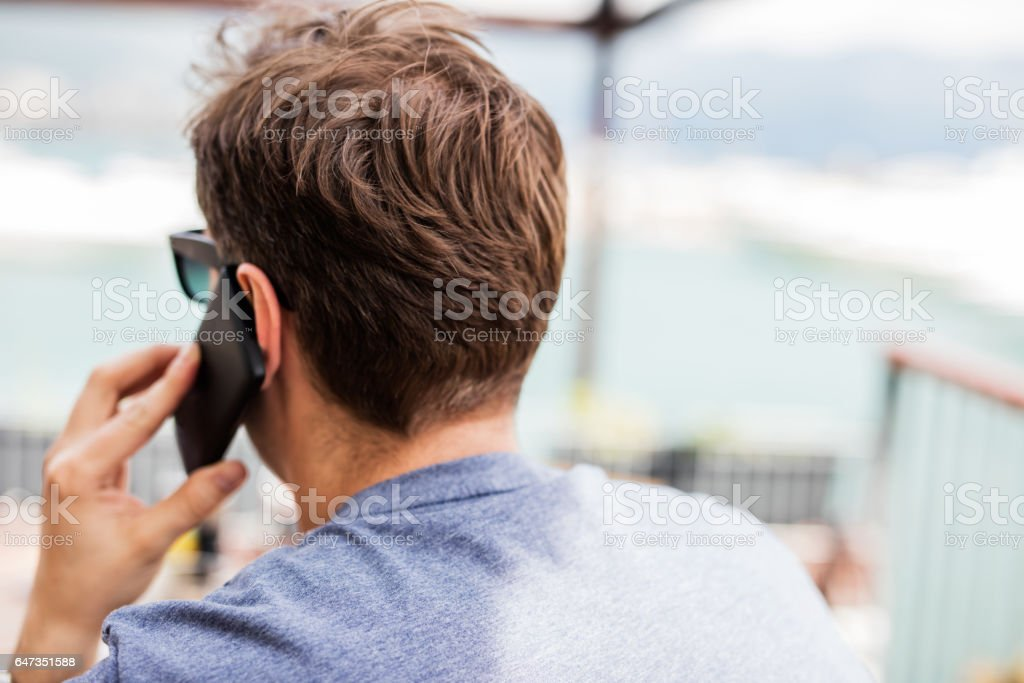 Rear view of business man in black. young man talking on mobile phone stock photo