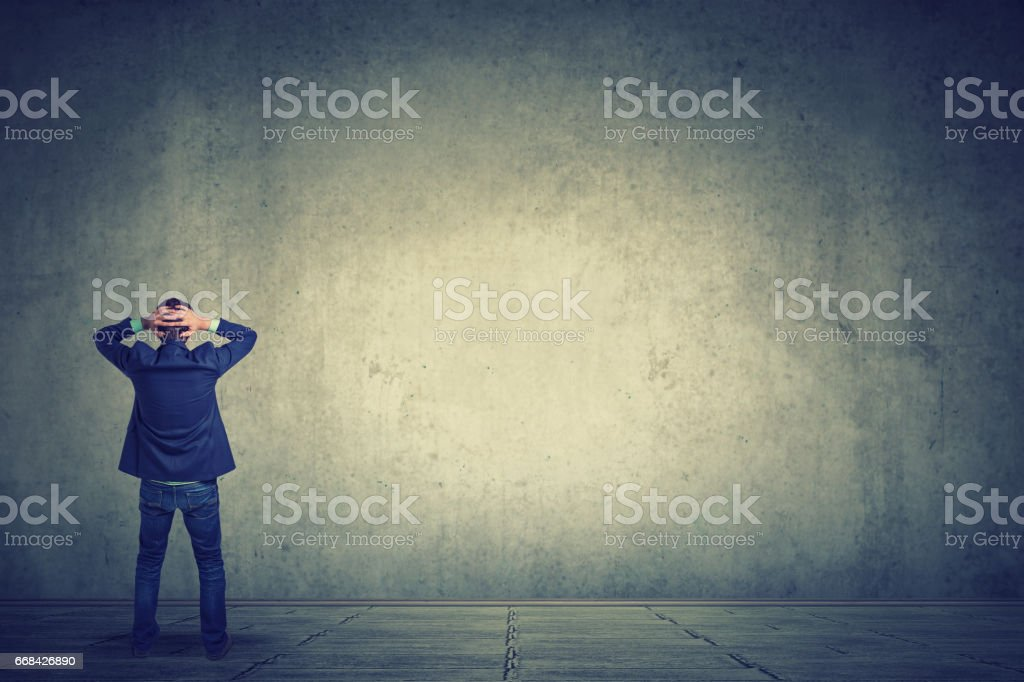 Rear view of business man standing in front of a wall hands on head wondering what to do next stock photo
