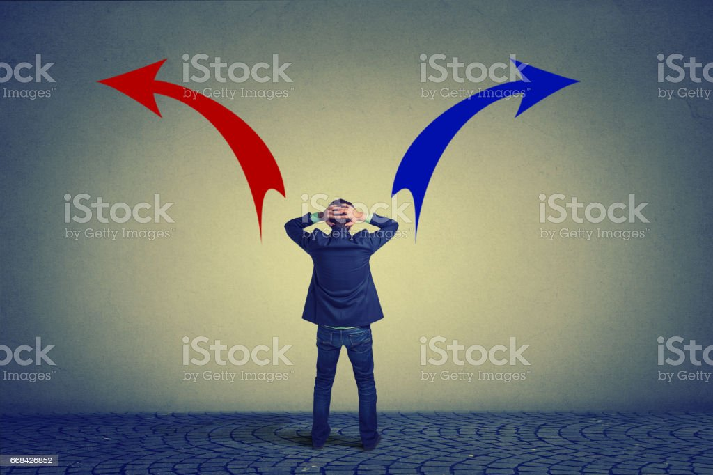 Rear view of business man standing in front of wall hands on head wondering which way to go stock photo