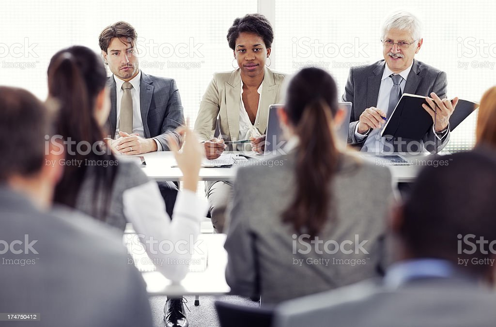 Rear view of business people attending a conference  raising  hands royalty-free stock photo
