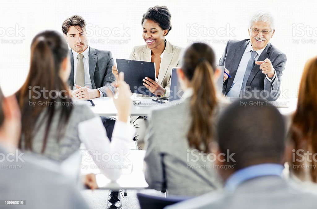 Rear view of business people attending seminar and raising  hands royalty-free stock photo