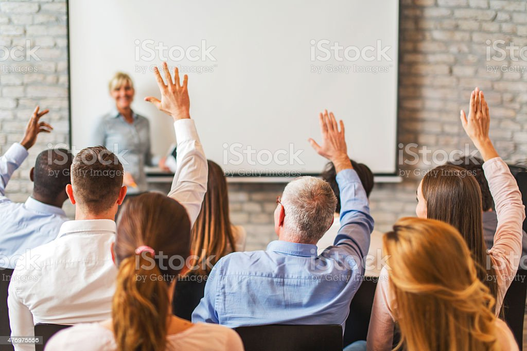 Rear view of business people with raised arms on seminar. stock photo