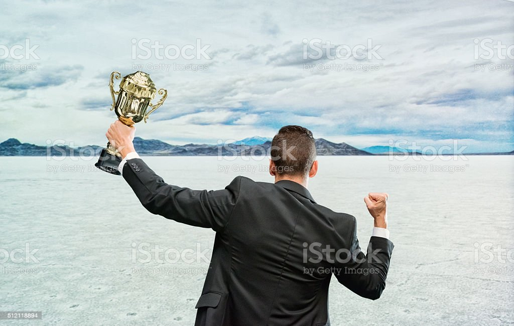 Rear view of businessman cheering with trophy stock photo
