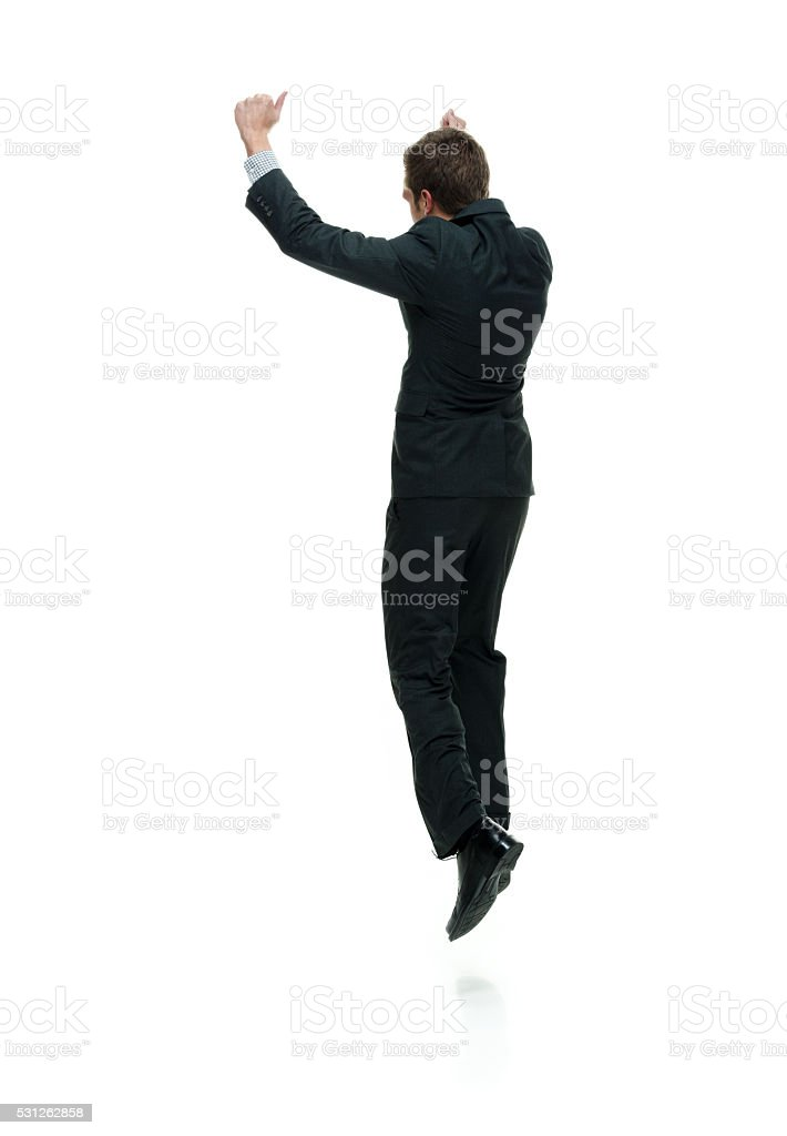 Rear view of businessman jumping and cheering stock photo