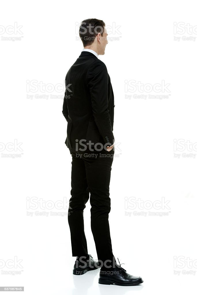 Rear view of businessman standing & looking away stock photo