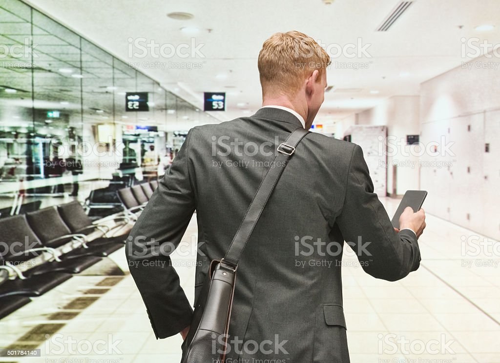 Rear view of businessman using tablet in airport stock photo