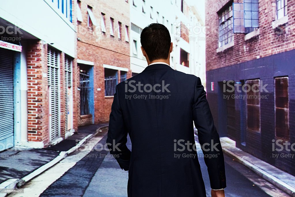 Rear view of businessman walking at street stock photo