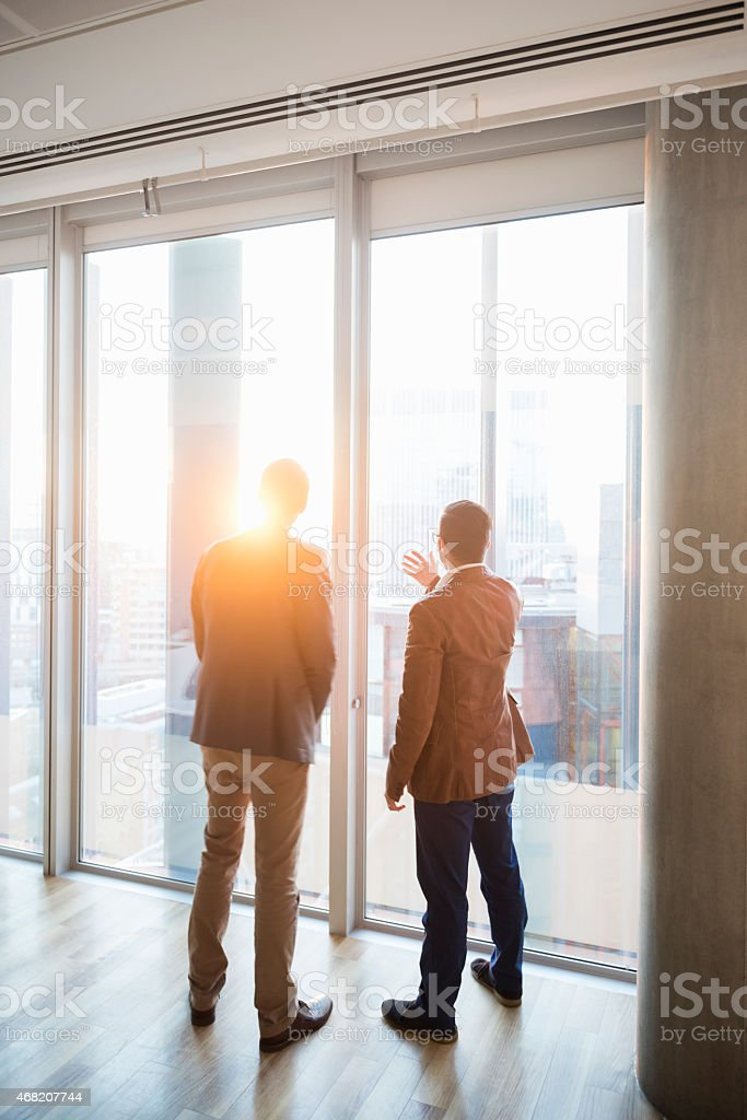 Rear view of businessmen admiring city through window stock photo