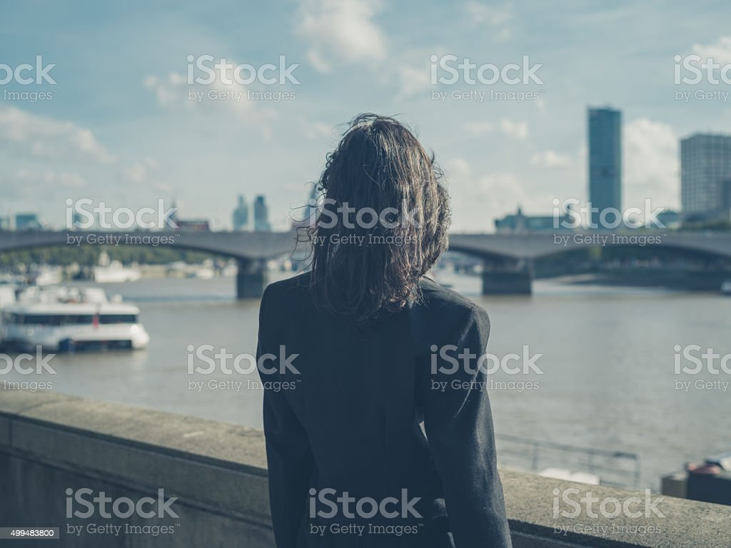 Rear view of businesswoman by river in city stock photo