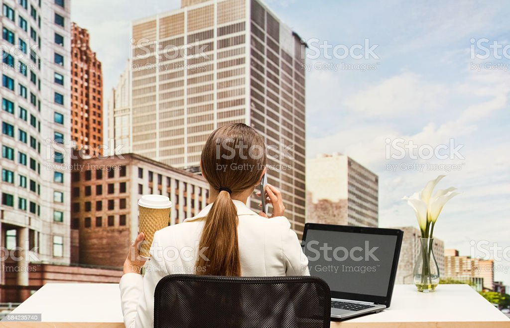 Rear view of businesswoman on phone outdoor stock photo