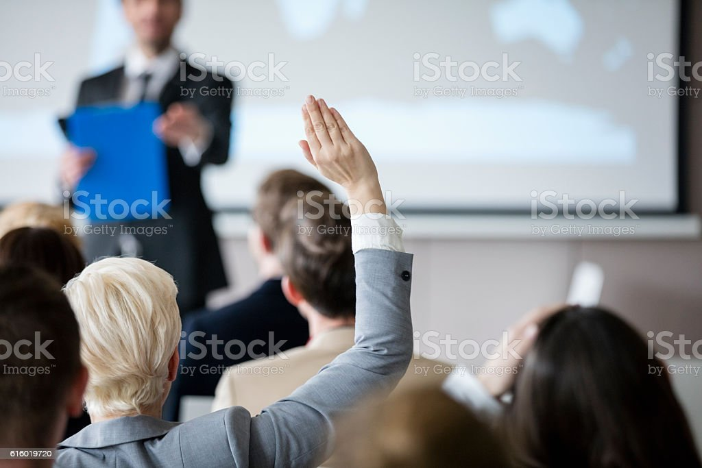 Rear view of businesswoman raising hand during seminar stock photo