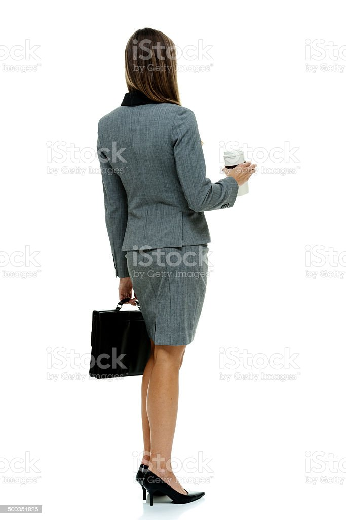 Rear view of businesswoman standing with coffee cup stock photo