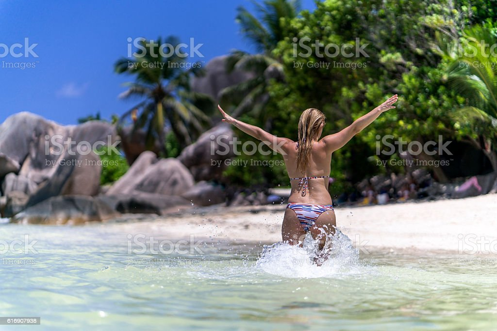 Rear view of carefree woman running through the sea. stock photo