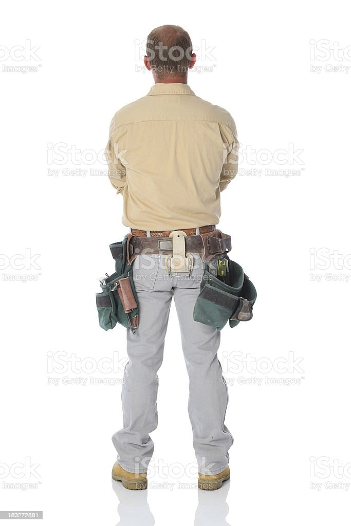 Rear view of carpenter standing with arms crossed royalty-free stock photo