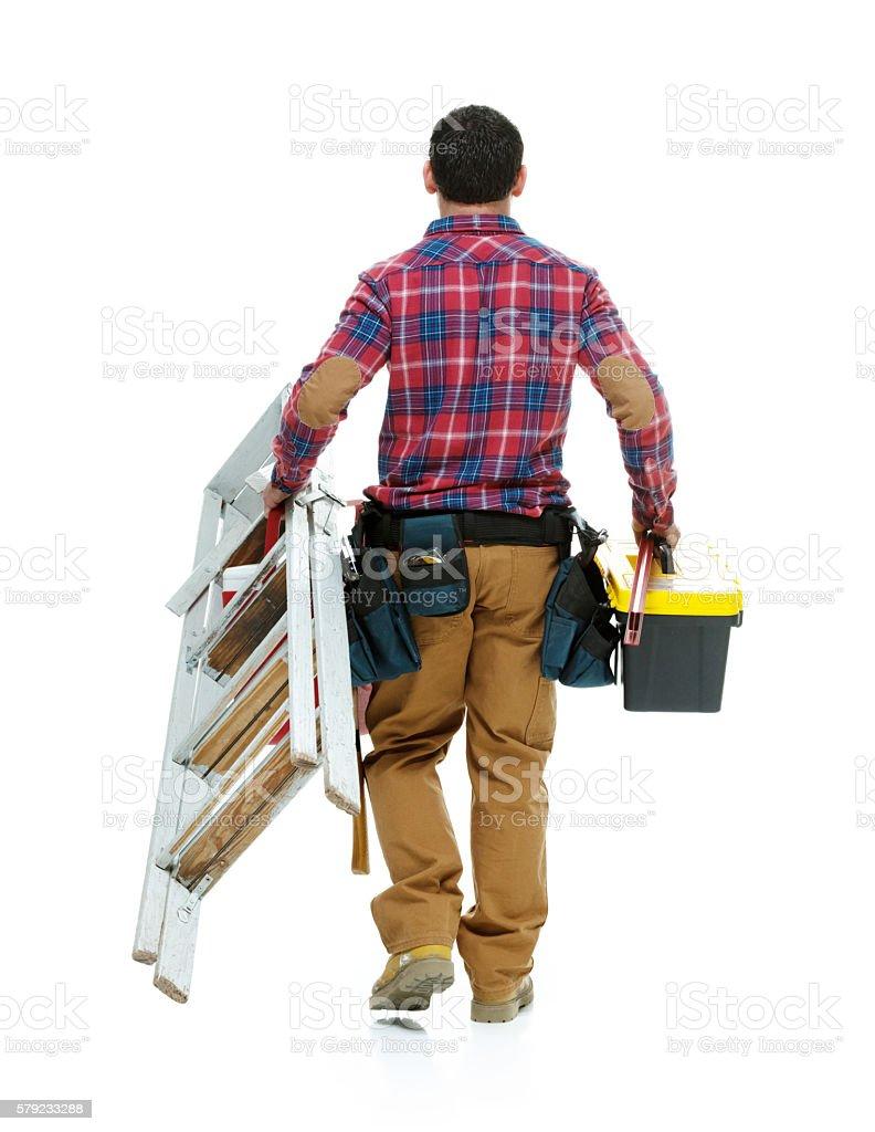 Rear view of carpenter walking stock photo