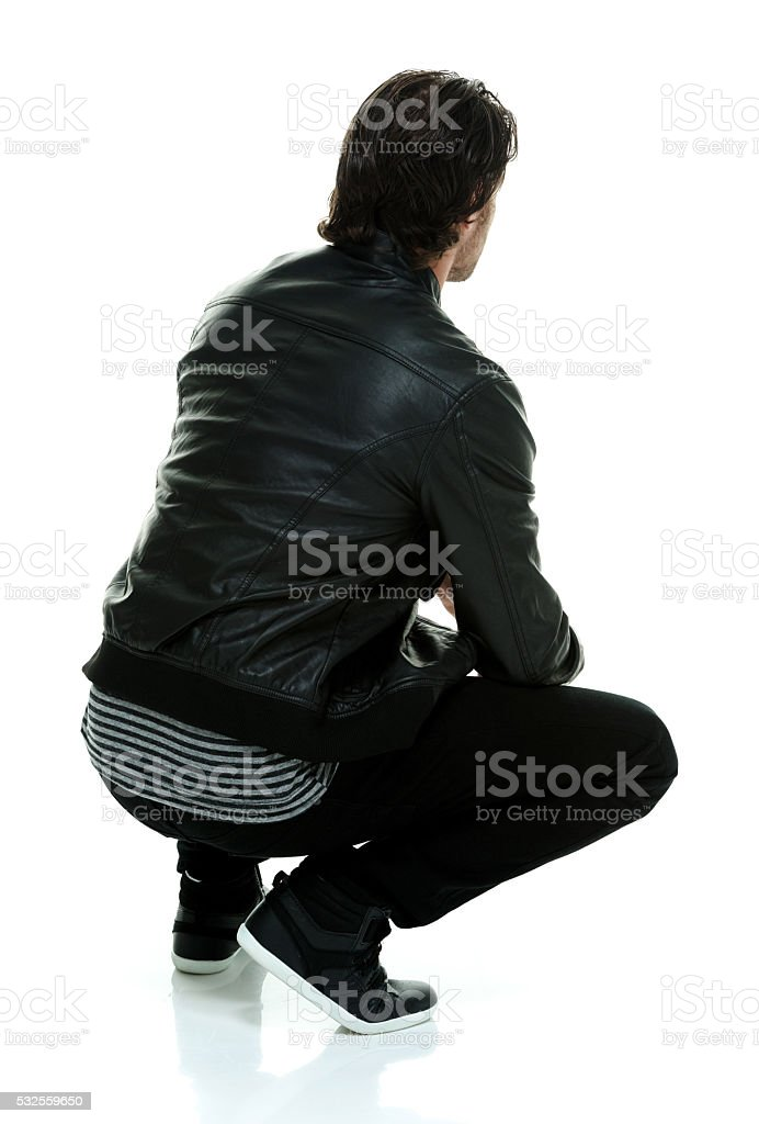 Rear view of casual man crouching stock photo
