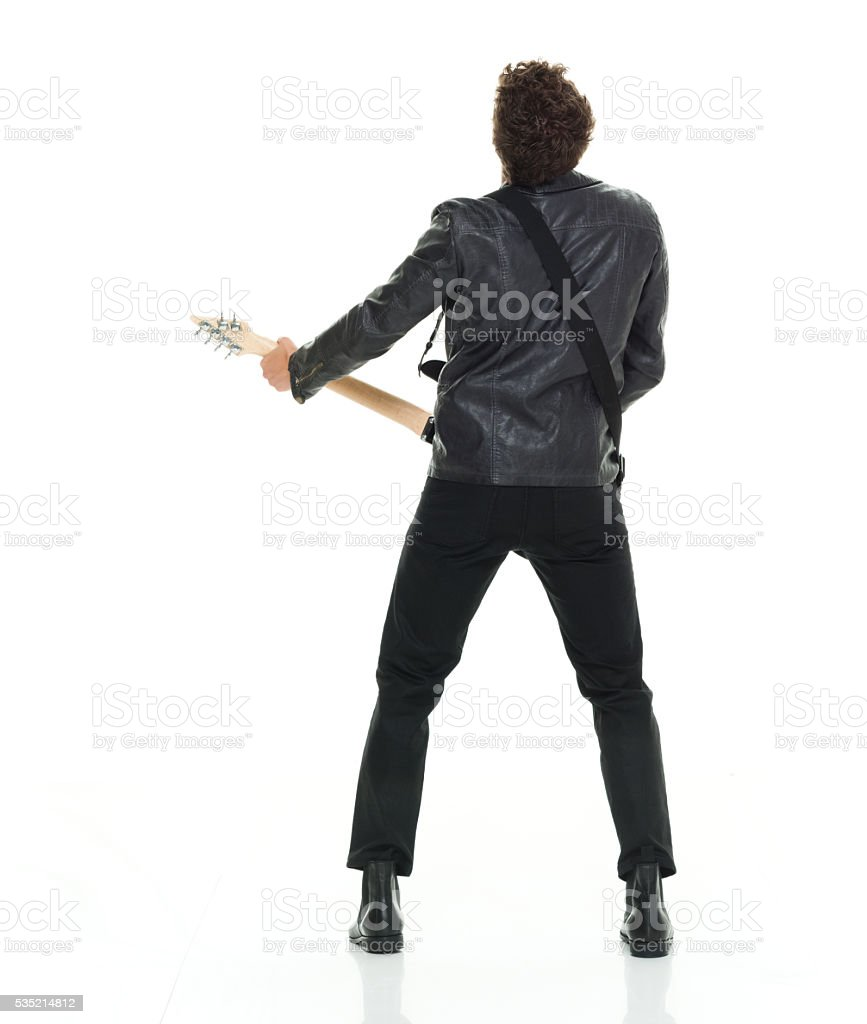 Rear view of casual man playing guitar stock photo