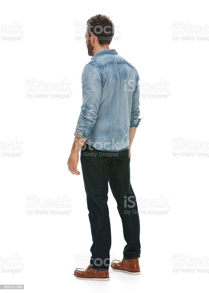 Rear view of casual man standing and looking away stock photo