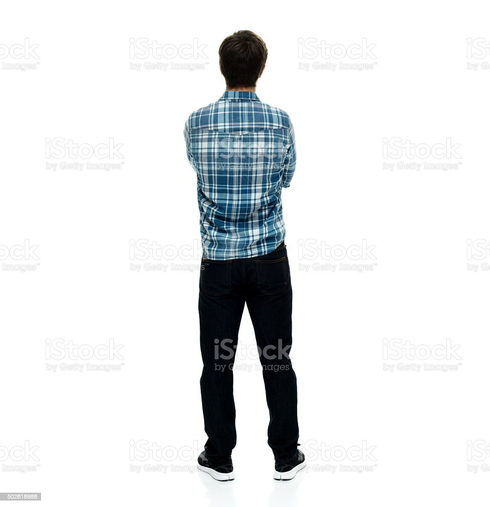 Rear view of casual man standing with arms crossed stock photo