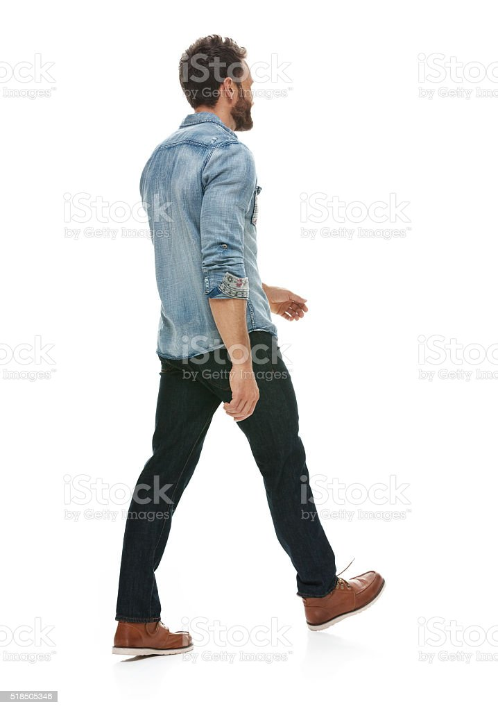 Rear view of casual man walking stock photo